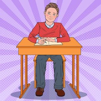 Uczeń siedzi przy ławce szkolnej