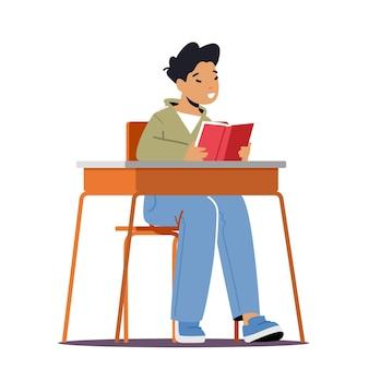 Uczeń w szkolnej klasie, mały uczeń siedzący przy biurku z otwartym podręcznikiem w rękach lekcja czytania