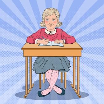 Uczennica siedzi przy ławce szkolnej
