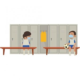 Uczniowie odpoczywają w szatni szkolnej sali gimnastycznej, jednocześnie używając maski medycznej i zachowując dystans społeczny