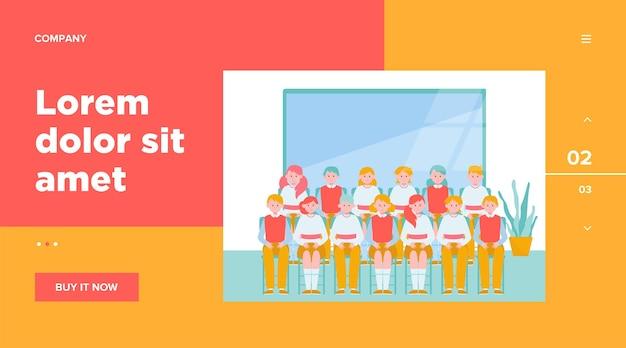 Uczniowie pozują do zdjęcia klasowego w klasie. nastoletni chłopcy i dziewczęta w mundurach siedzi w rzędach w pobliżu tablicy. ilustracja wektorowa pamięci, kolegów z klasy, koncepcja edukacji