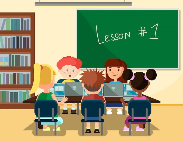 Uczniowie uczący się online w klasie z laptopami.
