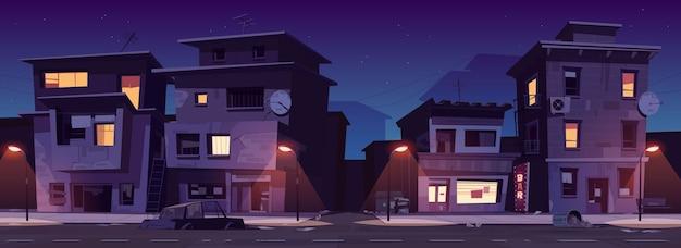 Ulica getta nocą, slumsy zrujnowane, opuszczone stare budynki ze świecącymi oknami. zniszczone mieszkania stoją na poboczu drogi z latarniami ulicznymi, karoserią i ilustracją kreskówki wektorowej śmieci