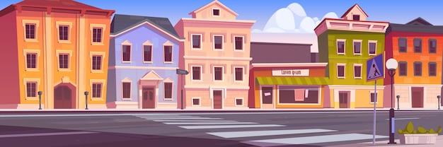 Ulica miejska z domami, pusta droga samochodowa i przejście dla pieszych