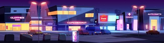 Ulica miejska ze sklepami i budynkami handlowymi w nocy. rysunkowy pejzaż z kawiarnią, biblioteką, apteką, supermarketem i parkingiem z samochodami oświetlonymi światłami ulicznymi. wieczorne miasteczko ze sklepami
