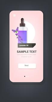 Upuszczając niezbędną szklaną butelkę olejku lawendowego z fioletowym kwiatem i płynnym naturalnym środkiem do pielęgnacji ciała, koncepcja smartfona ekran aplikacja mobilna pionowo