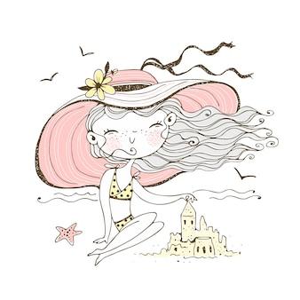 Urocza dziewczyna w kapeluszu na plaży buduje zamek z piasku. podróżować.