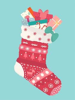 Urocza płaska różnorodność prezentowych pudeł w czerwonej skarpecie świątecznej, szczęśliwego nowego roku i wesołych kart świątecznych
