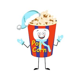 Urocza popcornowa postać w świątecznym pudełku ze szczęśliwymi emocjami, radosną twarzą, uśmiechniętymi oczami, rękami i nogami. zabawna przekąska do kina i filmów. symbol szczęśliwego nowego roku w czerwonym kapeluszu, szaliku i rękawiczkach świętego mikołaja