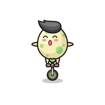 Urocza postać jajka w cętki jedzie na rowerze cyrkowym, ładny styl na koszulkę, naklejkę, element logo