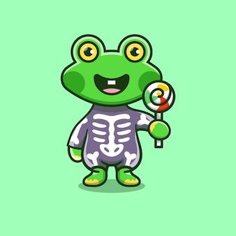 Urocza żaba ubrana w szkieletowy kostium na halloween i niosąca lizaka