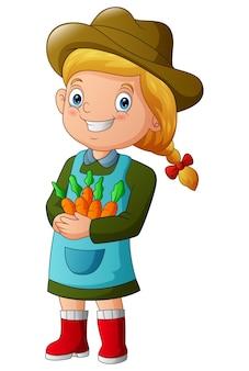 Uśmiechnięta rolnik dziewczyna trzyma kilka ilustracji marchwi