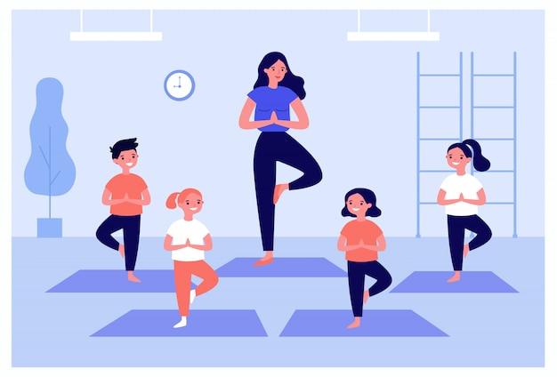 Uśmiechnięte dzieci ćwiczenia w zajęciach jogi