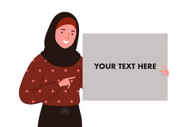 Uśmiechnięty hidżab lub muzułmańskie kobiety trzymające białą pustą tablicę lub płótno jedną ręką
