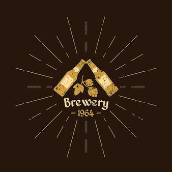 Vintage logo piwa. browar. butelki piwa, liście chmielu i tekst na brązowym tle