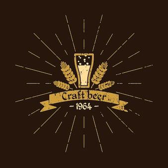 Vintage logo piwa. browar. szklanka do piwa, liście chmielu i tekst na wstążce na brązowym tle