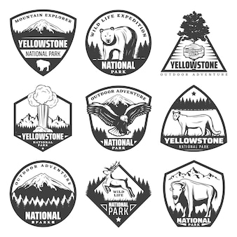 Vintage monochromatyczne etykiety parków narodowych z napisami rzadkie zwierzęta drzewa góry eksplodujące gejzer na białym tle