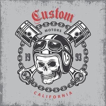 Vintage motocyklowy nadruk z czaszką w kasku motocyklowym i skrzyżowanymi tłokami na tle folwarku.