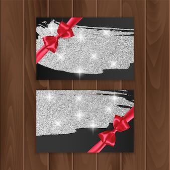 Voucher, karta podarunkowa ze srebrnym połyskiem i czerwoną kokardką