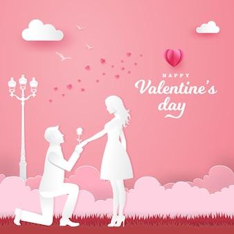 Walentynki kartkę z życzeniami. młody mężczyzna klęczy do swojej dziewczyny i daje różę w parku z sercem i różem
