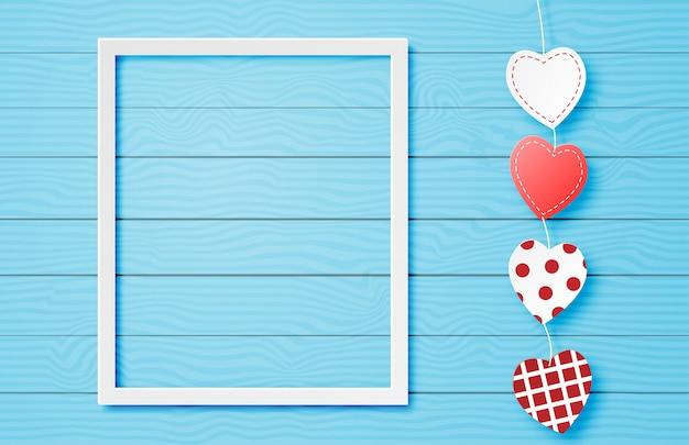 Walentynki transparent z wiszącym kształcie serca i ramki na niebieskim tle w stylu cięcia papieru.