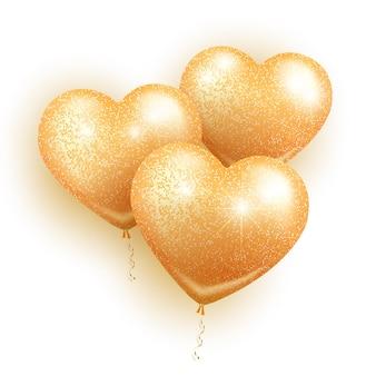 Walentynki. trzy złote balony w kształcie serca ze złotym brokatem i błyskami. na białym tle.