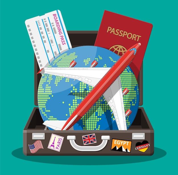Walizka podróżna z naklejkami przedstawiającymi kraje i miasta z całego świata. glob z celami podróży. samolot, bilet i paszport. urlop i wakacje.