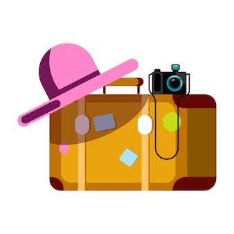 Walizka z różowym kapeluszem i aparat fotograficzny na białym tle