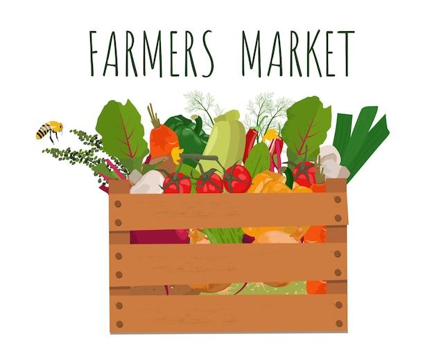 Warzywa w drewnianym pudełku. zbiory, lokalne produkty naturalne. reklama targu rolnego.