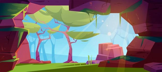 Wejście do jaskini w dżungli z zielonymi drzewami, trawą, mchem i błękitnym niebem