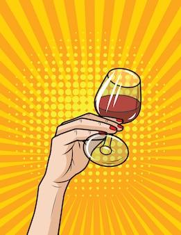 Wektor retro ilustracja komiks stylu pop-art kieliszek czerwonego wina. ręka ze szklanką alkoholu