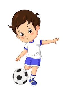 Wektorowa ilustracja kreskówka małego chłopca grającego w piłkę nożną