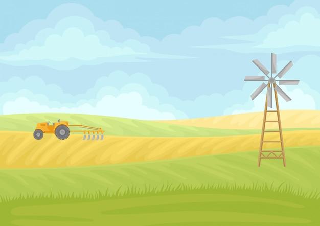Wentylator i żółty traktor z pługiem w polu.