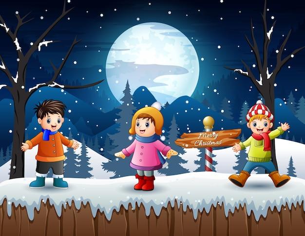 Wesołe dzieci bawiące się w śnieżny zimowy krajobraz