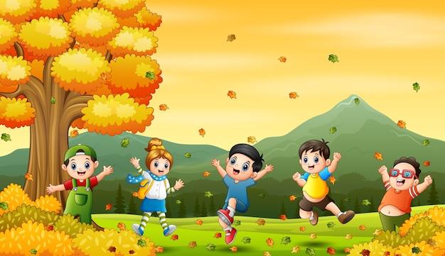 Wesołe małe dzieci skaczą i śmieją się w jesiennym krajobrazie