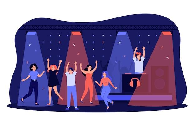 Wesoły młodzi ludzie tańczą w dyskotece, ciesząc się nocną imprezą, uroczystością.