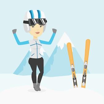 Wesoły narciarz stojący z podniesionymi rękami.