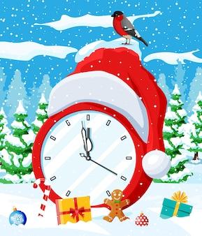Wesołych świąt bożego narodzenia i nowego roku kartkę z życzeniami świątecznymi z zegarem. czapka świętego mikołaja, pudełko prezentowe, drzewo, piłka i piernikowy ludzik, ptak gil. zimowy krajobraz leśny. ilustracja wektorowa płaskie