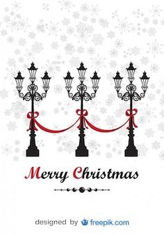 Wesołych świąt bożego narodzenia kartkę z życzeniami z ozdobnym latarni i padający śnieg tła