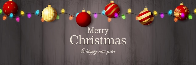 Wesołych świąt bożego narodzenia transparent z czerwonymi kulkami na szarym drewnianym podłożu