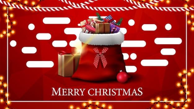 Wesołych świąt, czerwona kartka z życzeniami z wielokątną teksturą i worek świętego mikołaja z prezentami