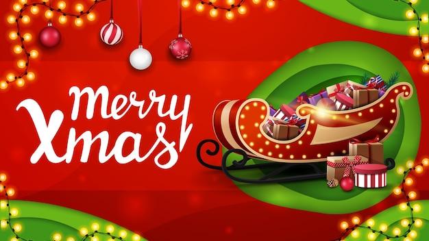 Wesołych świąt, czerwono-zielony baner rabatowy w stylu wycinanym z papieru z girlandami, bombkami i saniami mikołaja z prezentami