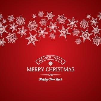 Wesołych świąt i nowego roku karty pozdrowienie napis i płatki śniegu o różnych kształtach na czerwono