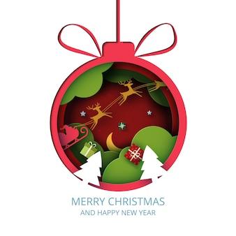 Wesołych świąt i sezonu zimowego na czerwonym tle czerwona bombka ozdobiona pudełkiem i mikołajem w saniach sztuka papieru