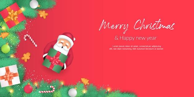 Wesołych świąt i szczęśliwego nowego roku. gałązki choinkowe ozdobione cukierkami, pudełkami na prezenty i kulkami z trzmieli. święty mikołaj trzyma pudełko i udekorowany na czerwonym tle.