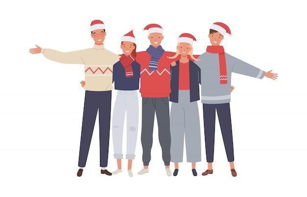 Wesołych świąt i szczęśliwego nowego roku. grupa przyjaciół młodych ludzi przytulanie razem na imprezie wakacyjnej.