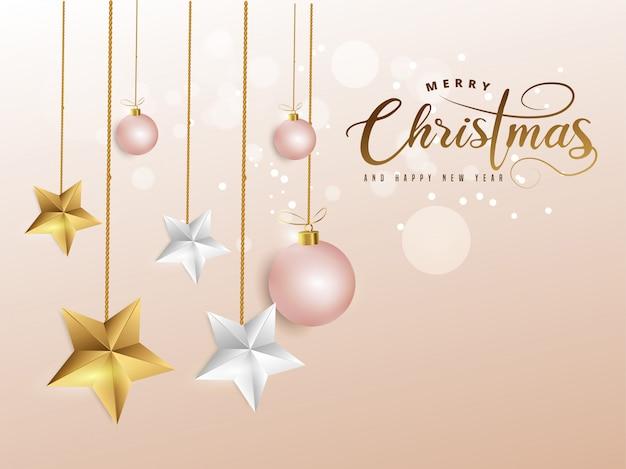 Wesołych świąt i szczęśliwego nowego roku napis na miękkim różu ozdobiony bombkami i złotymi, białymi gwiazdami.