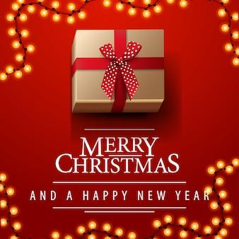 Wesołych świąt i szczęśliwego nowego roku pocztówka z czerwonym kwadratem z girlandą i prezentem z kokardą