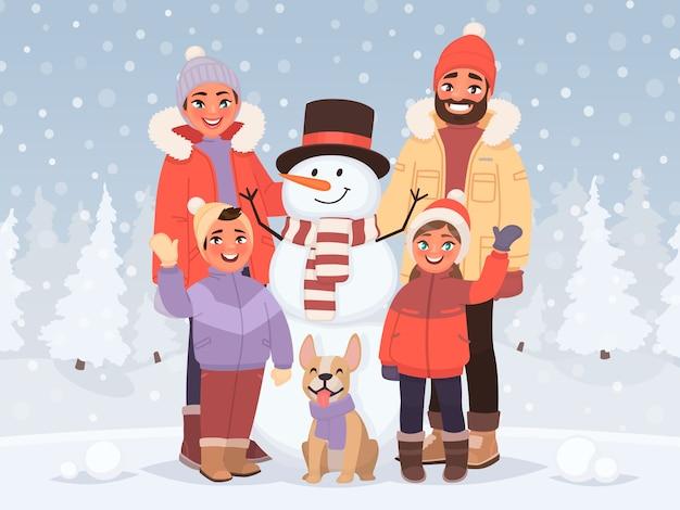 Wesołych świąt i szczęśliwego nowego roku. rodzina w zimowym krajobrazie stoi obok bałwana.