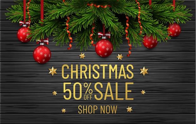 Wesołych świąt i szczęśliwego nowego roku sprzedaż transparent. obramowanie choinki ze złotymi dekoracjami na czarnym drewnie